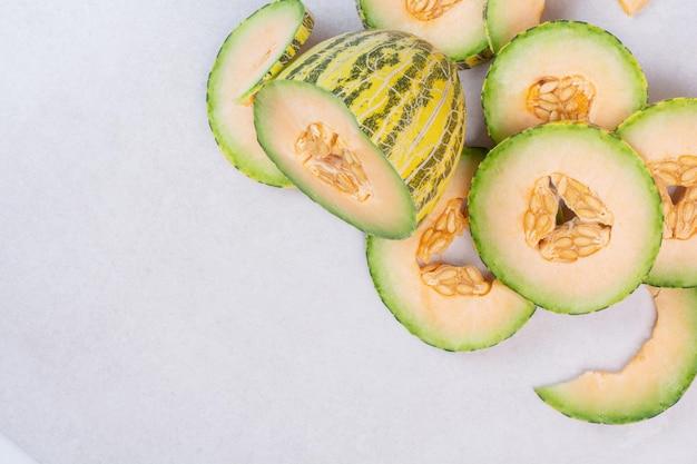 Posiekany zielony melon na białym stole.