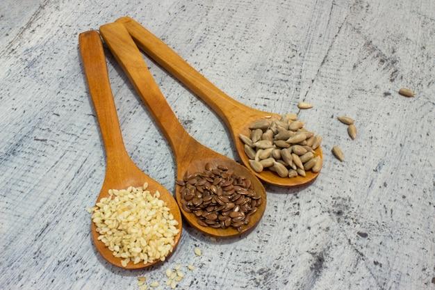Posiew. nasiona w drewnianej łyżce. ziarna słonecznika. kminek, benni, sezam