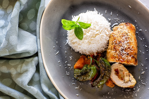 Posiłki: obiad i kolacja. jedzenie gotowe do spożycia. roladki z kurczaka z ryżem i warzywami