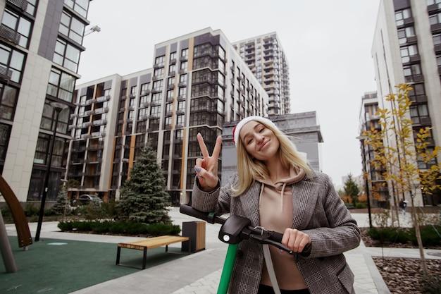 Posing for photo młoda wesoła blondynka pokazując znak pokoju i patrząc na kamery z uśmiechem. szare nowoczesne bloki mieszkalne na tle. jeździ skuterem elektrycznym.