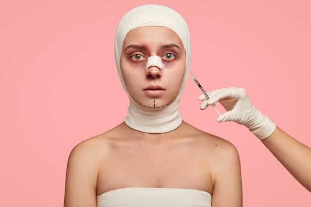 Posiniaczona młoda kobieta w bandażach otrzymuje zastrzyk w okolicę twarzy, wypełnia twarz kolagenem, przeszła operację powiek, modelowanie nosa i redukcję podbródka