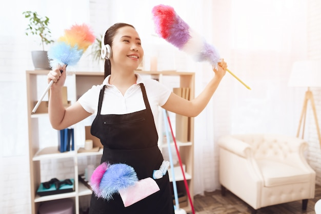 Positive maid in earphones with feather dusters.