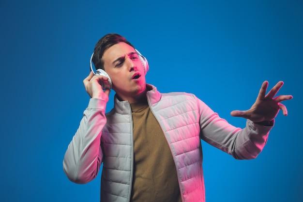 Posłuchać muzyki. portret mężczyzny rasy kaukaskiej na niebieskiej ścianie studia