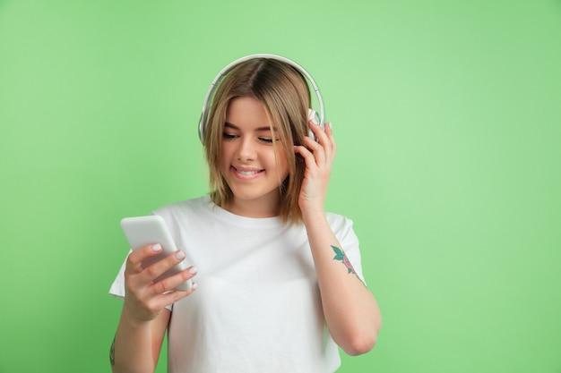 Posłuchać muzyki. portret młodej kobiety rasy kaukaskiej na białym tle na zielonej ścianie. piękne modelki w białej koszuli.