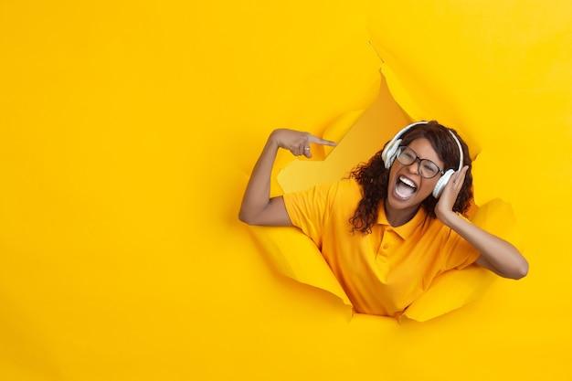 Posłuchać muzyki. wesoła afro-młoda kobieta w rozdartym tle żółtego papieru, emocjonalna, ekspresyjna. przełamanie, przełom. pojęcie ludzkich emocji, wyraz twarzy, sprzedaż, reklama.