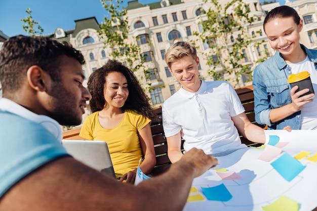 Posłuchaj mnie. zachwyceni uczniowie siedzący na ławce i uśmiechający się na twarzach, patrząc na papier whatmana