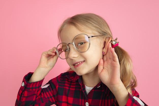 Posłuchaj sekretów. kaukaski portret małej dziewczynki na różowej ścianie. piękna modelka z blond włosami.