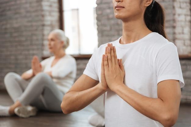 Posłuchaj swoich myśli. zdjęcie długowłosego mężczyzny noszącego białą koszulkę, trzymając plecy prosto podczas jogi.