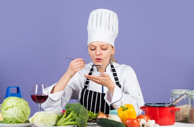 Posmakuj smaku. gotowy do gotowania nowego dania. świeża sałatka wegetariańska. kucharz w kuchni komercyjnej. profesjonalny kucharz ze zdrowymi produktami. szczęśliwy uśmiechający się kucharz przygotowuje posiłek z różnymi warzywami.