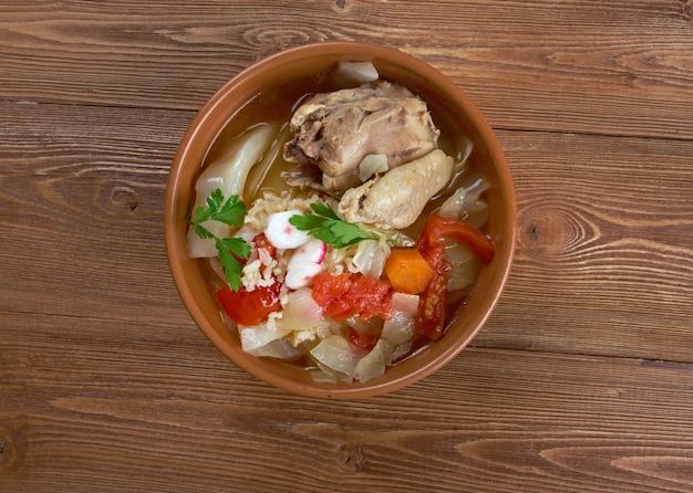 Posole z kurczaka przyozdobione marchewką, pomidorem i rzodkiewką.