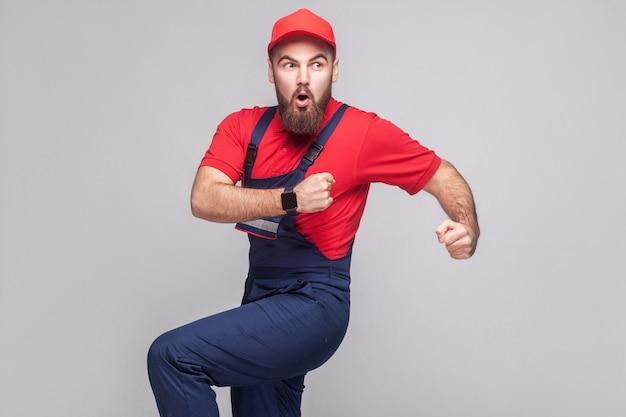 Pośpiesz się! młody zdumiony majsterkowicz z brodą w niebieskim kombinezonie, czerwonej koszulce i czapce spóźnia się i zaczyna biec po pomoc na czas. szare tło, wnętrze, studio strzał, na białym tle, kopia przestrzeń