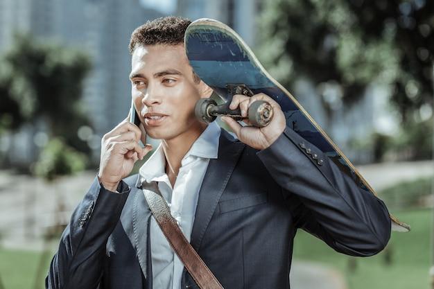 Pośpiesz się. uroczy student płci męskiej trzymając deskorolkę i komunikując się przez telefon