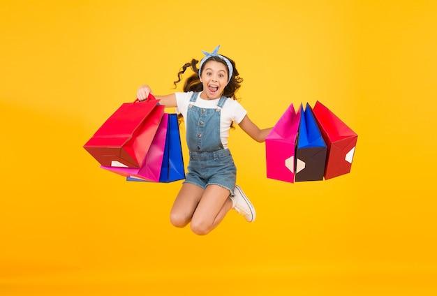 Pospiesz się z całkowitą sprzedażą. moda dziecięca. wyprzedaże i rabaty. szczęśliwa mała dziewczynka po udanych zakupach. energiczne dziecko skacze z ciężkimi torbami. prezenty świąteczne w paczkach. cyber poniedziałek. czas zakupów.