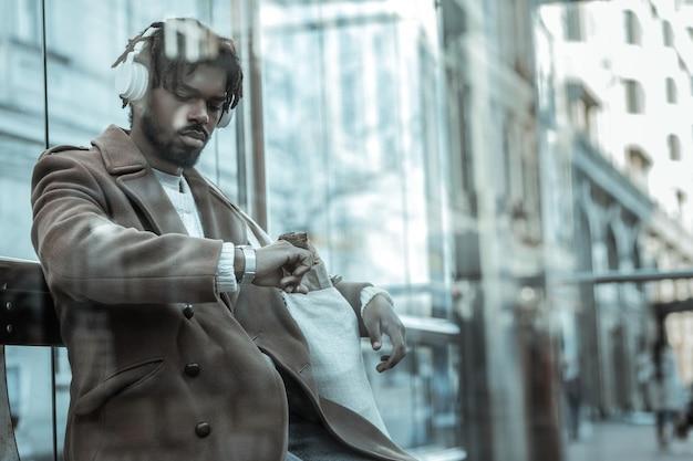 Pośpiesz się. zły międzynarodowy mężczyzna czeka na swój autobus i siedzi na stacji