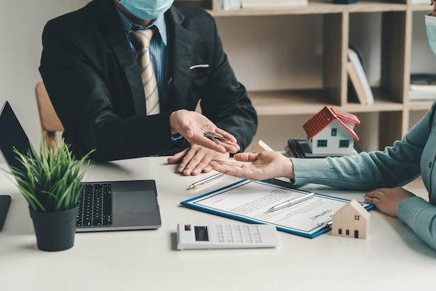 Pośrednicy w obrocie nieruchomościami dostarczają klientom klucze do domu umowy kupna-sprzedaży dokumenty umowy są wypełniane w biurze.