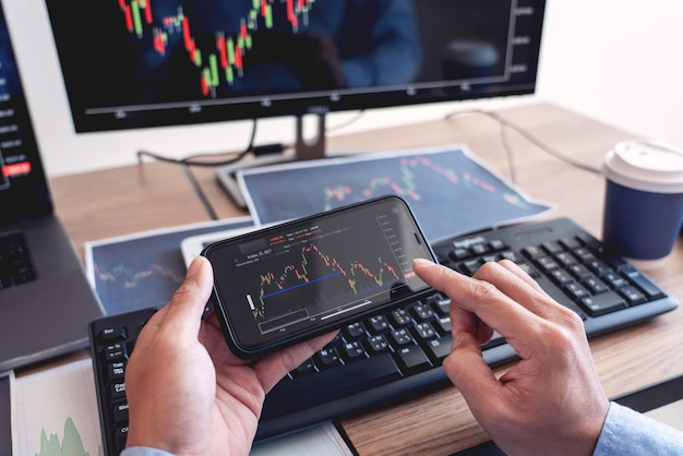 Pośrednik biznesmena analizowanie wykresów danych finansowych i raportów na ekranie