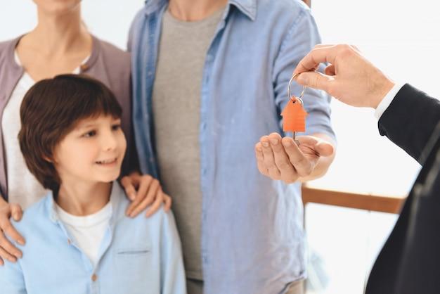 Pośrednik handlu nieruchomościami daje ojcu klucze do nowego mieszkania.