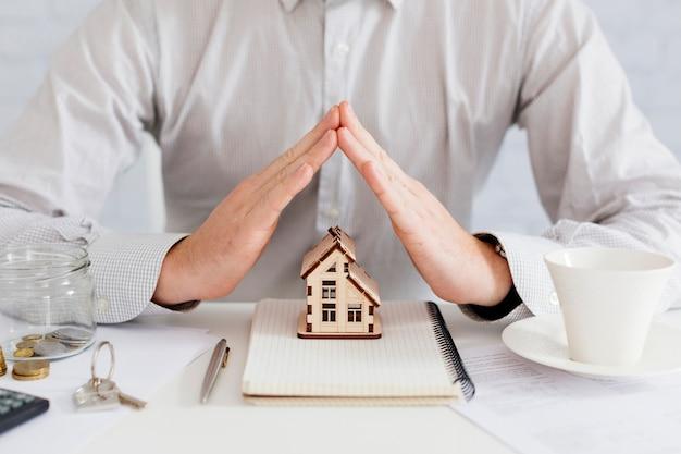 Pośrednik handlu nieruchomościami gestykuluje przy domem