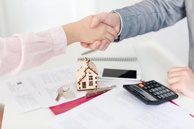 Pośrednik handlu nieruchomościami i klienta, ściskając ręce