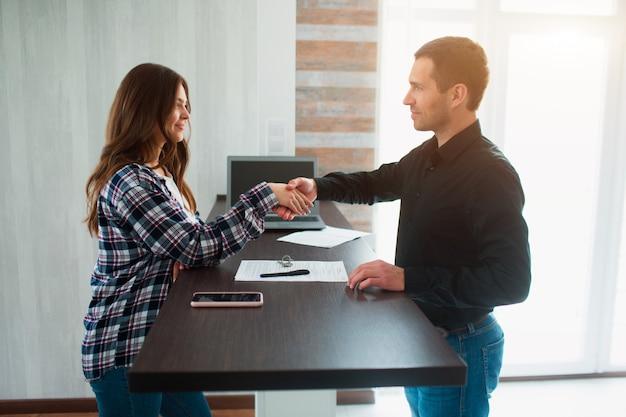 Pośrednik handlu nieruchomościami, pośrednik lub właściciel pokazuje mieszkanie młodej kobiecie. ma zamiar podpisać z nim umowę najmu. agent nieruchomości uścisk dłoni z klientem po podpisaniu umowy