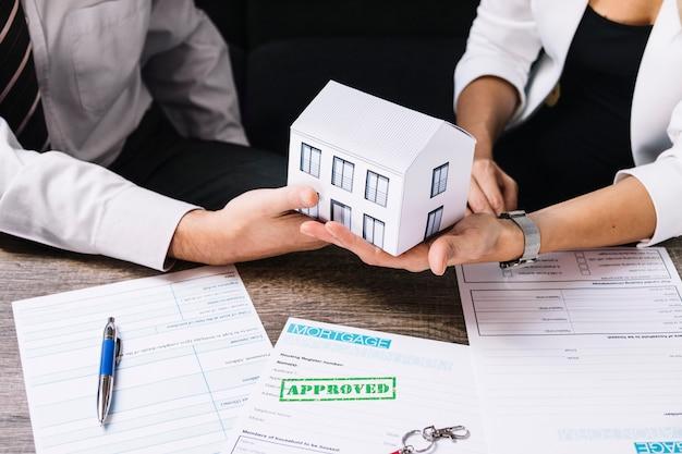 Pośrednik handlu nieruchomościami robi transakci z klientem w biurze