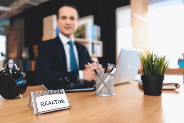 Pośrednik handlu nieruchomościami siedzi przy biurku w biurze. mężczyzna pozuje na aparacie.