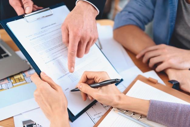 Pośrednik handlu nieruchomościami siedzi przy biurku z kontraktem na nowe mieszkanie.
