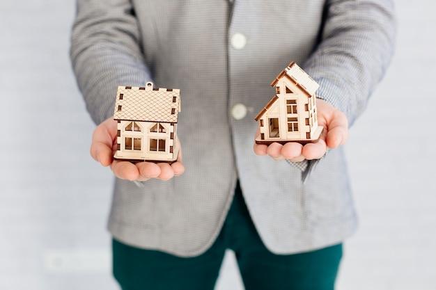 Pośrednik handlu nieruchomościami trzyma domowe figurki