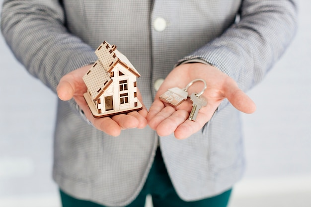 Pośrednik handlu nieruchomościami z domową figurką i kluczem