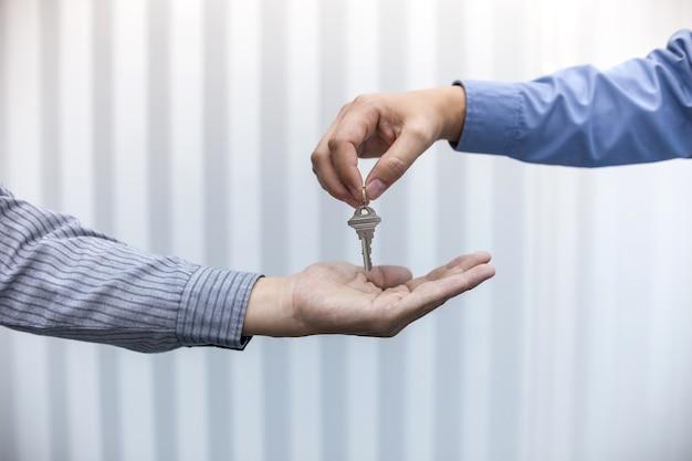Pośrednik w handlu nieruchomościami daje domów kluczom mężczyzna w biurze