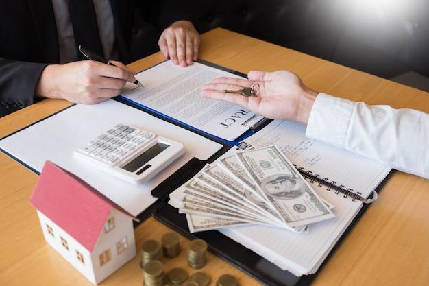 Pośrednik w handlu nieruchomościami daje domowi klucze klienta znaka zgody nieruchomość dla sprzedaży