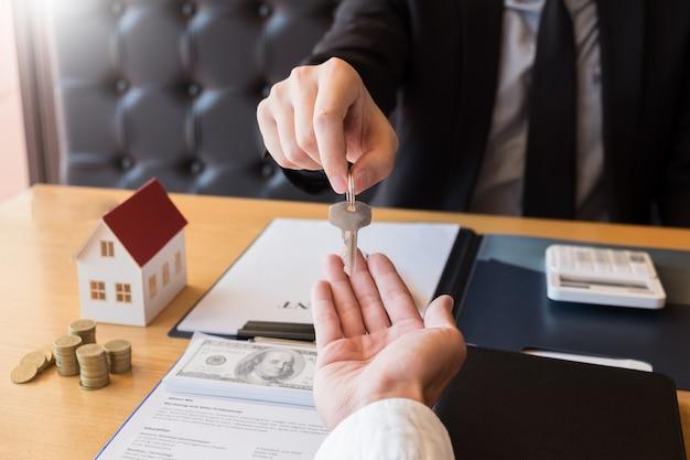 Pośrednik w handlu nieruchomościami daje domowi kluczowego klienta znaka zgody mieniu