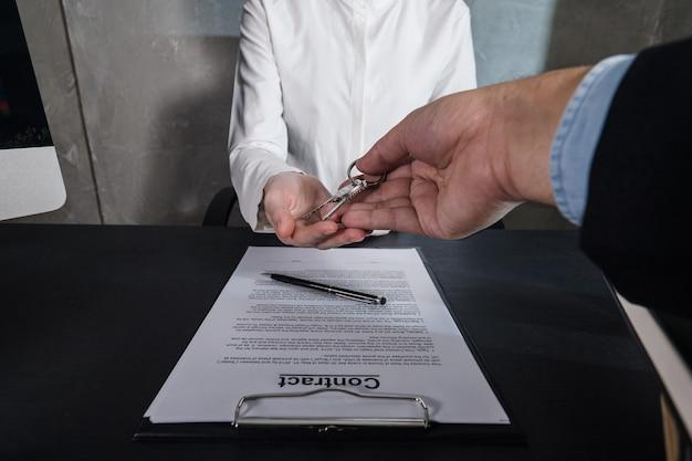 Pośrednik w handlu nieruchomościami daje klucze kobiecie właśnie wynajmującej lub kupującej nowy dom.