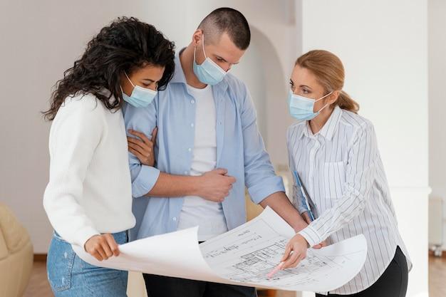 Pośrednik w handlu nieruchomościami i para z maskami medycznymi, patrząc na plany domów