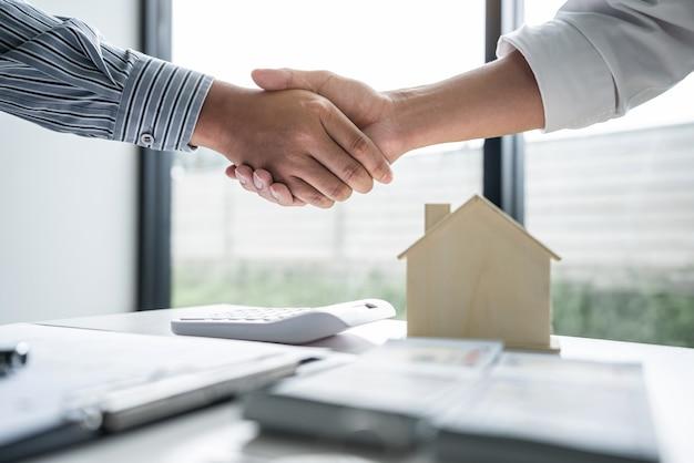 Pośrednik w obrocie nieruchomościami i klienci ściskają razem dłonie świętując skończoną umowę po podpisaniu