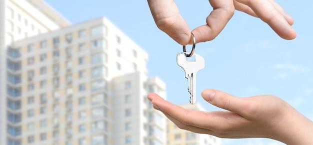 Pośrednik w obrocie nieruchomościami podający klucze do mieszkania do ręki kobiety na tle nowego wielopiętrowego budynku