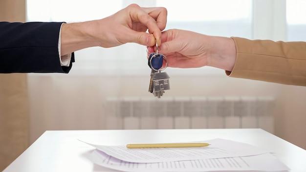 Pośrednik w obrocie nieruchomościami podaje rękę i daje klucze klientce nad stołem z podpisaną umową najmu mieszkania i długopisem w jasnym widoku biura