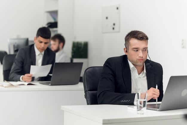 Pośrednik w obrocie nieruchomościami w miejscu pracy agencji prowadzi negocjacje z klientem przez internet i telefon