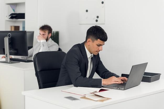 Pośrednik w obrocie nieruchomościami w miejscu pracy agencji prowadzi negocjacje z klientem przez internet i telefon.