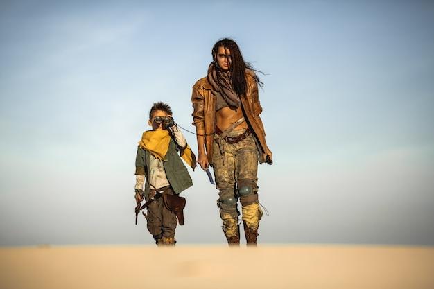 Post apokaliptyczna kobieta i chłopiec na zewnątrz na pustkowiu
