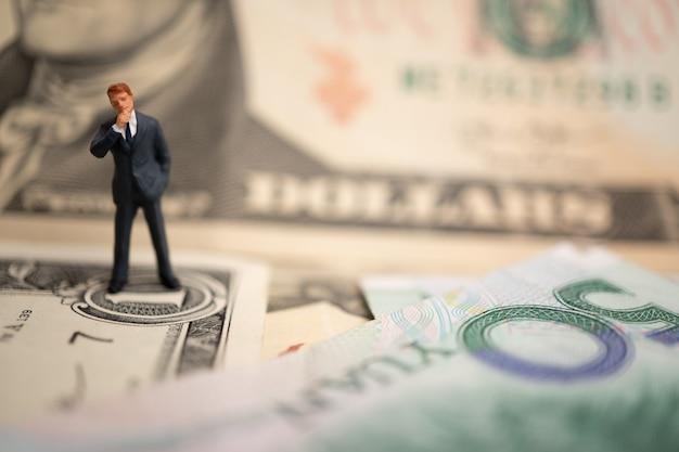 Postać biznesmena stojącego na dolarze amerykańskim i banknocie yuan trzymają ręce na sukces w umowach handlowych.