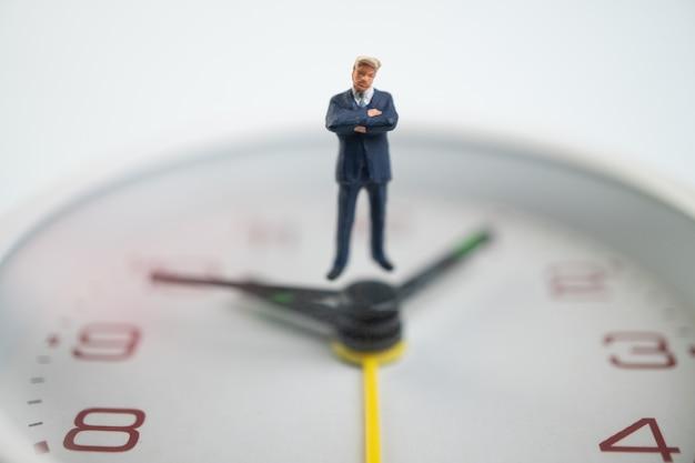 Postać biznesmenów myśli i stojąc na białej tarczy zegarka obok tarczy zegarka wskazującej czas.