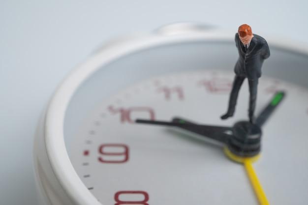 Postać biznesmenów patrzy, myśli i stoi na białej tarczy zegarka obok tarczy zegarka wskazującej czas.