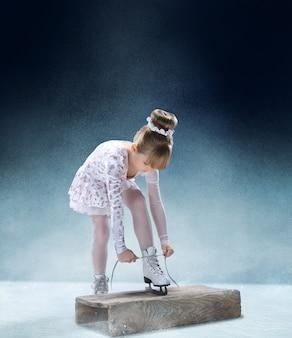 Postać małej dziewczynki sznuruje buty na hali lodowej. taniec, sport, zima, ćwiczenia, trening, dzieciństwo, mistrzowska koncepcja