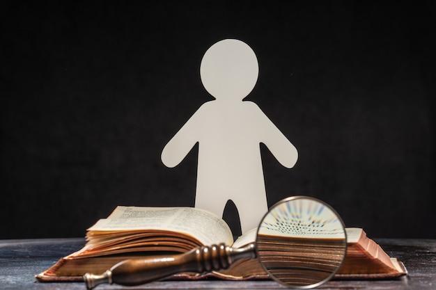 Postać mężczyzny wyrzeźbiona z papieru stojącego przy otwartej księdze. pojęcie uczenia się i wiedzy.