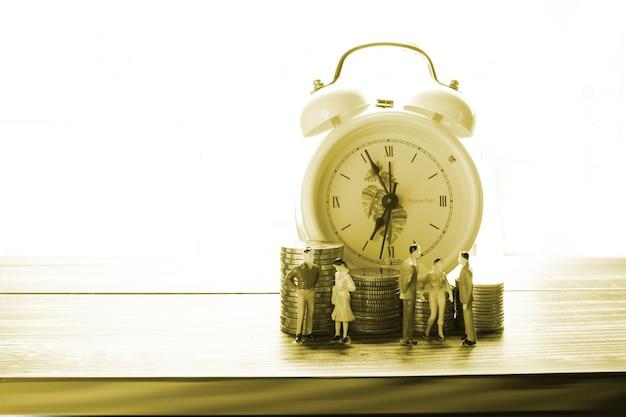 Postać modelu ludzi stojącego przed stosem monet z tłem budzika, ludzie oszczędzający pieniądze koncepcja