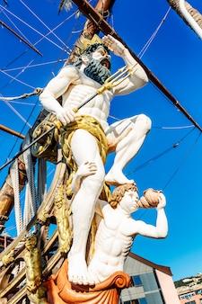 Postać neptuna na starym statku w porcie na tle błękitnego nieba. zbliżenie. pionowy.
