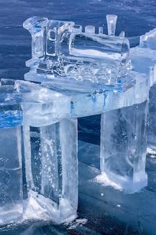 Postać starego parowozu z lodu stoi na lodzie jeziora bajkał. pociąg wykonany jest z czystego, niebieskiego lodu. pionowy.