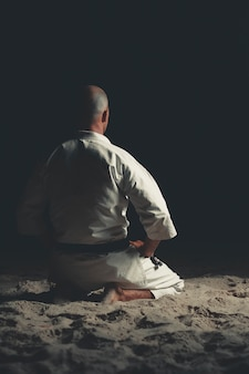 Postać w pozycji karate na czarnym tle.