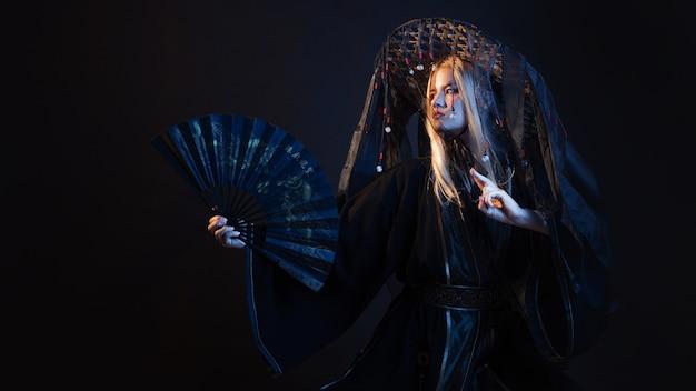 Postać w stylu azjatyckim w kimonie i słomkowym kapeluszu ze wstążkami w tanecznej pozie wykorzystuje wachlarza, młodą wieloetniczną samurajkę w stylu fantasy. zdjęcie studyjne na czarnym tle